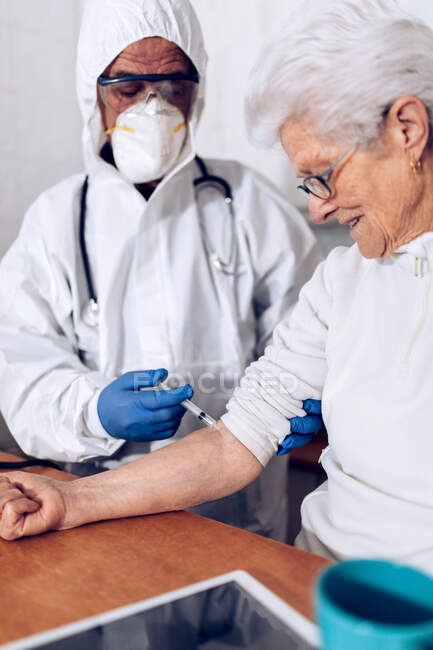 Професійний доглядальник чоловічої статі у захисній формі та рукавичках, які відвідують стареньку жінку вдома, та впорскування під час спалаху коронавірусу. — стокове фото