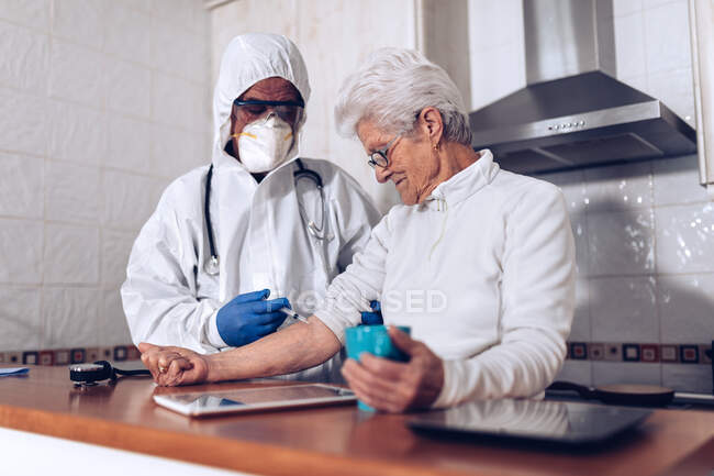 Caregiver making injection for senior patient at home — Stock Photo