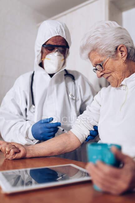 Cuidador que faz a injeção para paciente sênior em casa — Fotografia de Stock
