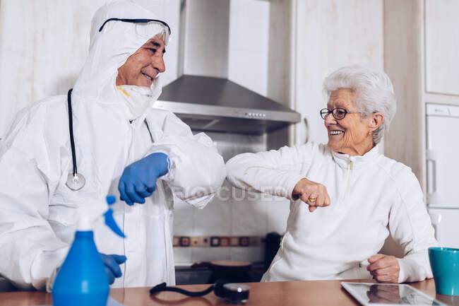 Positive gray haired female and professional male caregiver in protective uniform having fun and laughing while standing at kitchen counter during self isolation at home for coronavirus prevention — Stock Photo