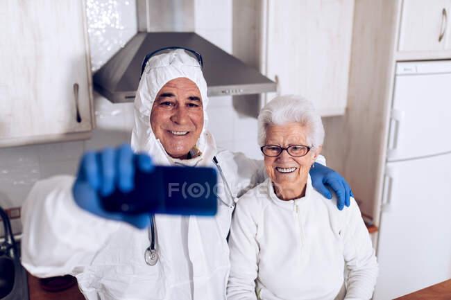 Especialista em cuidados domiciliares masculinos positivos em uniforme de proteção, abraçando paciente idosa sorridente e tomando selfie no smartphone enquanto estão juntos na cozinha doméstica durante o surto de coronavírus — Fotografia de Stock