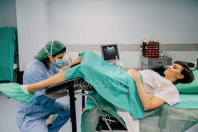 Side view of female doctor in blue uniform and sterile mask examining smiling patient on gynecological chair in fertility clinic — Stock Photo
