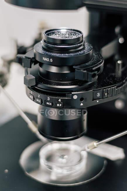 Объектив современной машины над чашкой Петри и манипуляторами в процессе оплодотворения яйцеклетки в современной лаборатории клиники — стоковое фото
