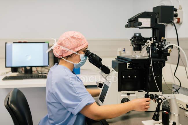 Vista lateral de la mujer en uniforme médico y máscara utilizando una máquina moderna para fertilizar los óvulos durante el trabajo en el laboratorio de la clínica de fertilidad moderna - foto de stock