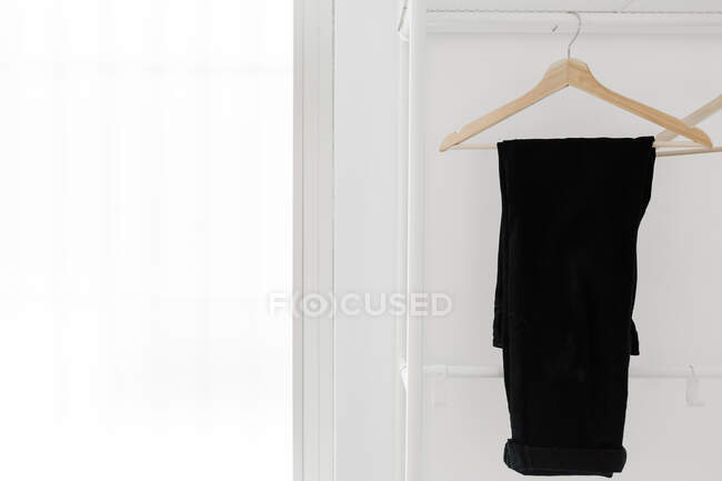 Hanger with stylish black trousers hanging on rail against white wall in light room — Stock Photo