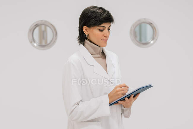 Side view of positive medical practitioner using tablet while standing against white door in hallway of modern hospital — Stock Photo