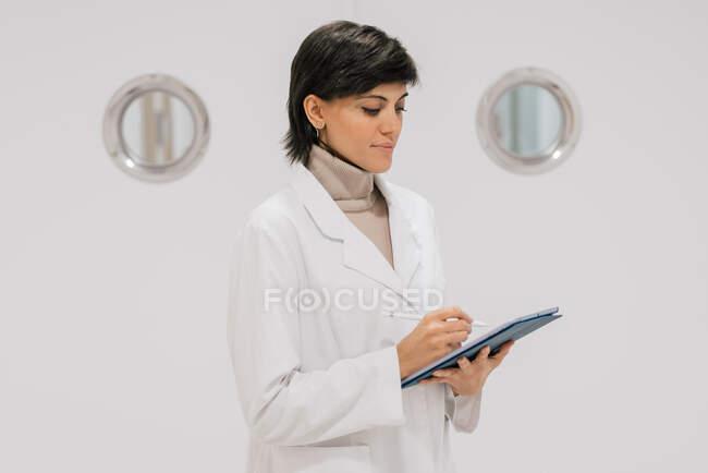 Vue latérale du médecin positif utilisant la tablette tout en se tenant contre la porte blanche dans le couloir de l'hôpital moderne — Photo de stock