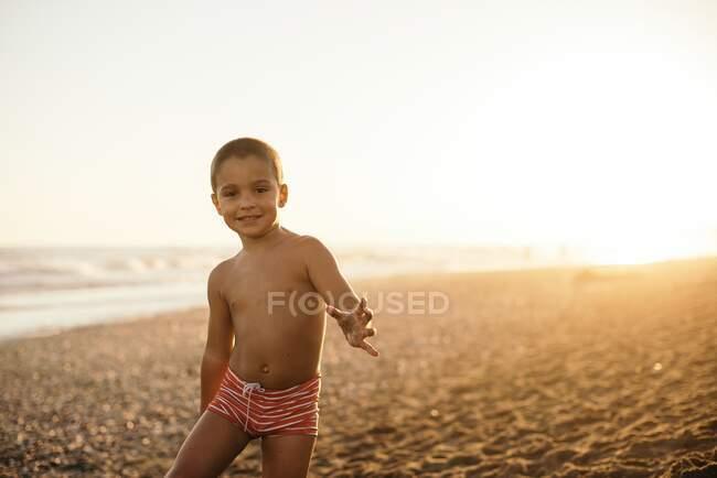 Счастливый мальчик без рубашки улыбается и смотрит в камеру, стоя на песчаном пляже во время заката — стоковое фото