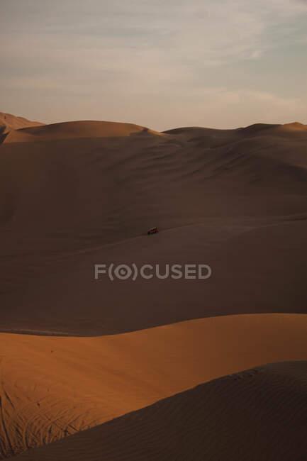 Pittoresca vista di dune di sabbia secca con strada solitaria e guida in auto nel deserto del Perù soleggiato in serata — Foto stock