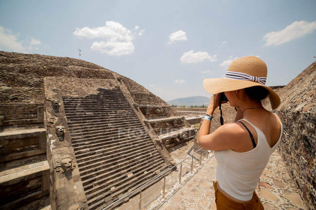 Side view of young anonymous female traveler in casual clothes and straw hat taking pictures of old ancient stone stairs with photo camera while visiting sunny Mexico — Stock Photo