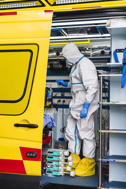 Vista lateral del médico anónimo en traje de protección de pie en el coche de ambulancia cerca de la puerta abierta con el equipo y examinar al paciente con infección por virus - foto de stock