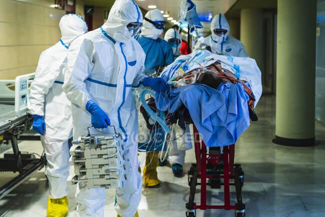 Grupo de médicos profissionais irreconhecíveis vestindo máscaras protetoras e uniformes transportando paciente com infecção viral através do corredor na clínica para a sala de cirurgia — Fotografia de Stock