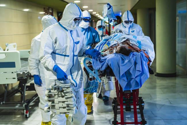 Grupo de médicos profesionales irreconocibles que llevan máscaras protectoras y uniformes que transportan al paciente con infección viral a través de la sala de operaciones en la clínica - foto de stock