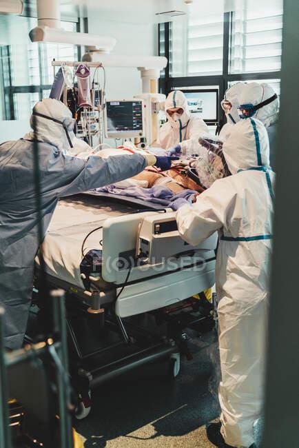 Médicos profissionais irreconhecíveis em uniformes e máscaras protetoras cuidando de pacientes com infecção viral em pé na sala de cirurgia no hospital moderno — Fotografia de Stock