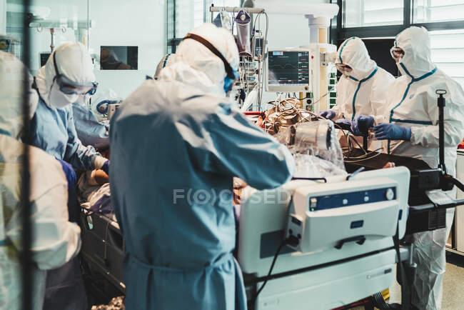Médicos profesionales irreconocibles con uniformes protectores y máscaras que cuidan al paciente con infección viral mientras está de pie en el quirófano en el hospital moderno - foto de stock