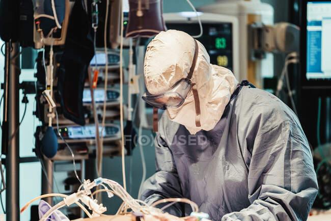 Visão lateral de médico profissional irreconhecível em uniformes de proteção e máscaras cuidando de paciente com infecção viral enquanto está em pé na sala de cirurgia no hospital moderno — Fotografia de Stock