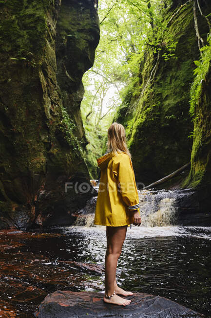 Side view of unrecognizable female traveler in yellow jacket standing in stone near cascade passing between mountains in sunlight looking away — Stock Photo