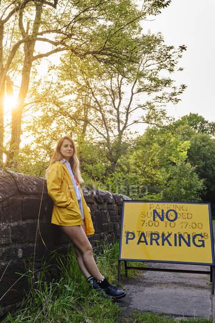 Mujer en chaqueta amarilla y pantalones cortos de mezclilla apoyada en una pared limpia una señal de tráfico No hay aparcamiento en la carretera rural en la tarde soleada de verano - foto de stock
