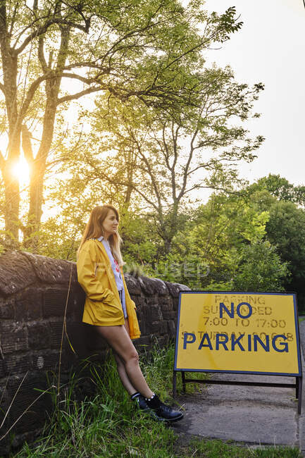 Female in yellow jacket and denim shorts leaning in a wall neat a road sign No parking on rural roadway in sunny summer afternoon — Stock Photo