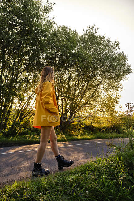 Side view of female in casual outfit with hands in pocket strolling on asphalt roadway in lush green countryside on sunny day and looking away — Stock Photo