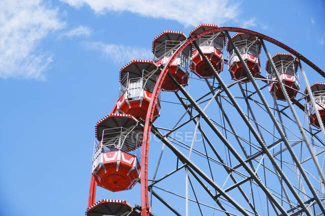 From below of Ferris wheel with red cabins located on amusement park on sunny day with blue sky — Stock Photo