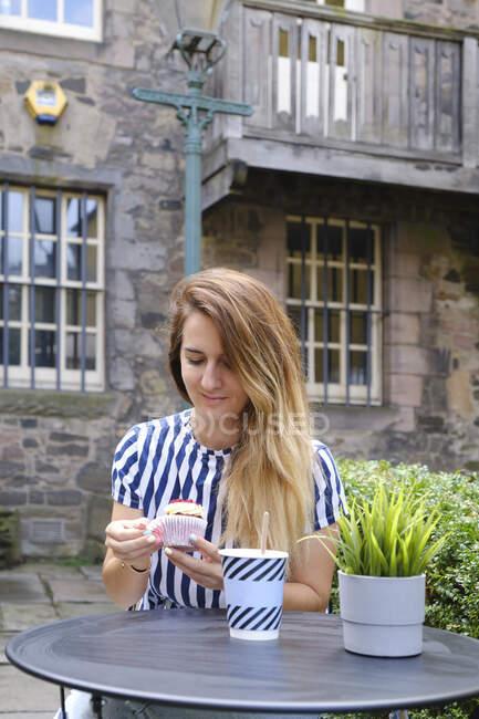 Donna sognante in abbigliamento casual mangiare cupcake guarnito con crema di burro e lamponi e bere bevanda calda da tazza usa e getta mentre seduto a tavola rotonda nella caffetteria di strada alla luce del sole — Foto stock