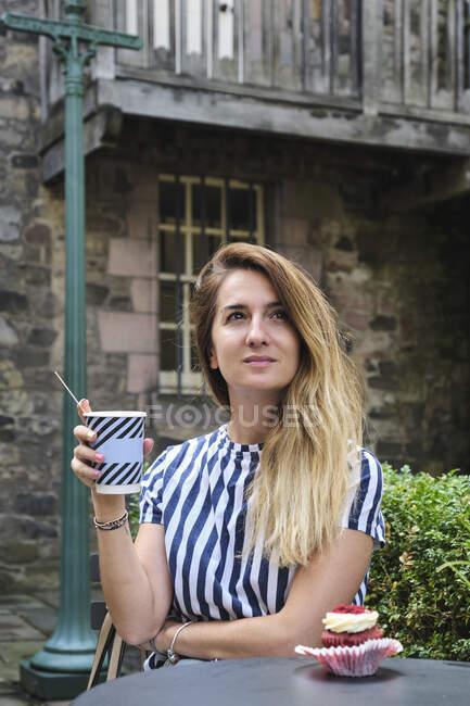 Мечтательная женщина в повседневной одежде пьет горячий напиток из одноразовой чашки, сидя за круглым столом с кексом, украшенным маслом и малиной в уличном кафе при солнечном свете — стоковое фото