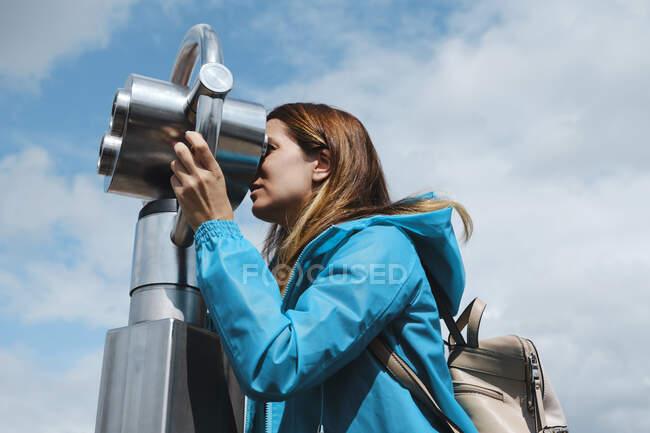 Mujer rubia anónima con abrigo azul mirando a través de la moneda de la calle operado binocular mientras está de pie en el pavimento de madera cerca de la valla de hormigón en el día soleado - foto de stock