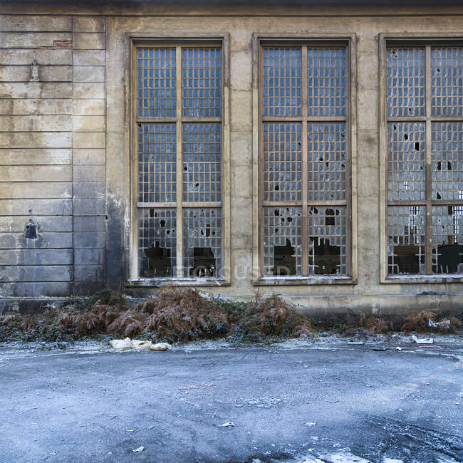 Exterior of abandoned stone industrial building with narrow windows with metal grid and broken glass — Stock Photo