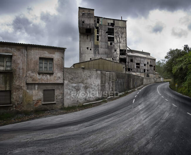 Old neglected industrial buildings with weathered stone walls located along curvy road in cloudy day in Spain — Stock Photo