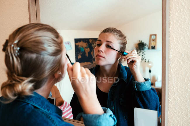 Back view of focused female in denim jacket looking in mirror and applying mascara make up against blurred interior of cozy modern apartment — Stock Photo