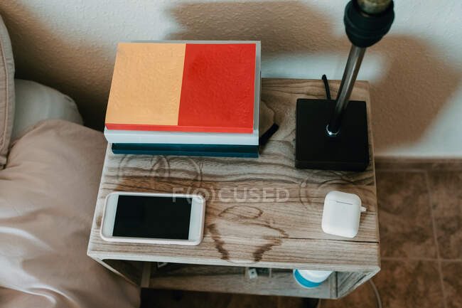 From above notebooks and smartphone in composition with true wireless earphones and lamp on wooden bedside table in cozy bedroom of modern apartment — Stock Photo