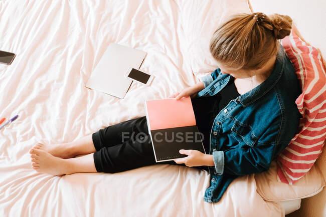 Сверху неузнаваемая женщина в черной повседневной одежде и джинсовой куртке, держащая открытый дневник с черными и розовыми страницами, отдыхая в одиночестве на мягкой кровати дома — стоковое фото