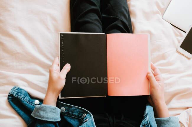 Из выше урожая неузнаваемая женщина в черной повседневной одежде и джинсовой куртке держа открытый дневник с черными и розовыми страницами, отдыхая в одиночестве на мягкой кровати у себя дома — стоковое фото