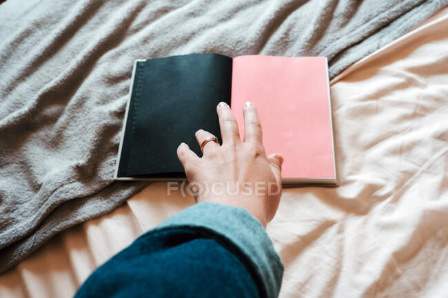 Сверху безликая женщина в повседневной одежде берет открытую тетрадь с пустыми черно-розовыми страницами из мягкой кровати в светлой современной спальне — стоковое фото