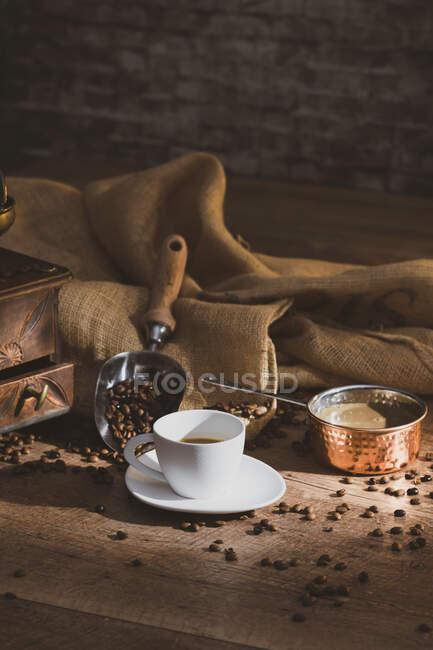 Café negro fresco en taza de cerámica blanca colocada en platillo cerca de molinillo de café y granos de café en mesa de madera - foto de stock