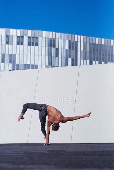 Задний вид неузнаваемого спортсмена без рубашки, выполняющего одну руку, выполняя упражнения против стены и синего неба на крыше современного здания — стоковое фото