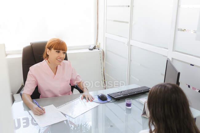 Positivo giovane segretaria donna in uniforme seduta alla scrivania vicino al computer e lavorare con i documenti mentre si parla con il cliente in luce moderna clinica dentale — Foto stock