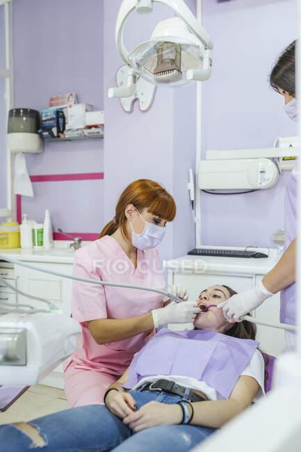 Dentista feminina de uniforme e máscara curando os dentes do paciente com assistente feminino na clínica odontológica moderna — Fotografia de Stock