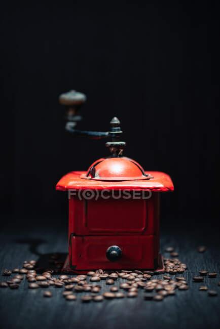Rote Vintage-Kaffeemühle aus Metall auf schwarzer Holzoberfläche mit frischen Kaffeekörnern im dunklen Raum auf dunklem Hintergrund — Stockfoto