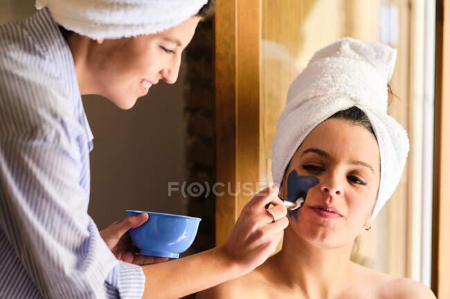 Fröhliche Frau, die eine Maske aus blauem Ton auf das Gesicht einer gelassenen Freundin aufträgt, die mit einem Handtuch im Kopf nach dem Bad wegschaut, während sie in der Nähe des Balkons im Sonnenlicht sitzt — Stockfoto