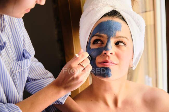 Anonyme Frau trägt blaue Lehmmaske auf Gesicht einer fröhlichen Frau auf, die während des Eingriffs zu Hause mit weißem Handtuch wegschaut — Stockfoto