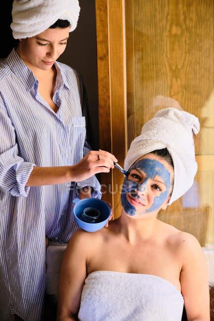 Weibchen tragen eine Maske aus blauem Ton auf das Gesicht einer gelassenen Freundin auf, die mit Handtuch im Kopf nach dem Bad in die Kamera blickt, während sie in der Nähe des Balkons im Sonnenlicht sitzt — Stockfoto