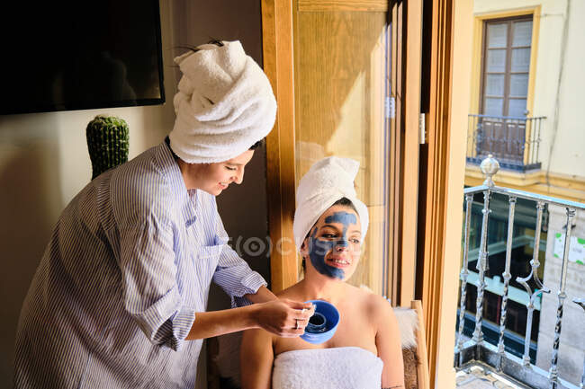 Cheerful female applying blue clay mask to face of content girlfriend with towel after bath while sitting near balcony in sunlight — Stock Photo