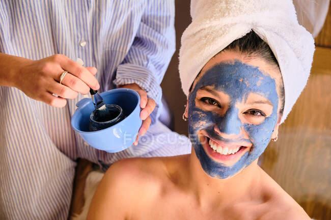 Mulher anônima aplicando máscara de barro azul no rosto de mulher alegre olhando para a câmera em toalha branca durante o procedimento em casa — Fotografia de Stock