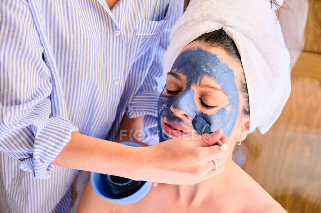 Side view of anonymous female applying blue clay mask to face of serene woman with closed eyes in white towel during procedure at home — Stock Photo