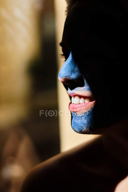 Crop cheerful lady with toothy smile and blue clay mask on face looking away in sunlight — Stock Photo