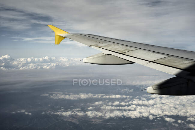 Wing of modern aircraft flying high above cloudy terrain with cloudy sky to sunny Ibiza — Stock Photo