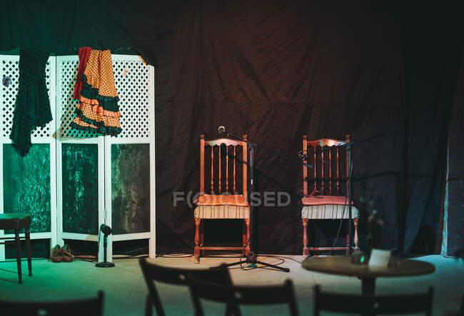 Leere Theaterbühne mit Holzstühlen und Flamencokleidern auf tragbarer Trennwand und mit Schuhen und Stehmikrofonen auf dem Boden — Stockfoto