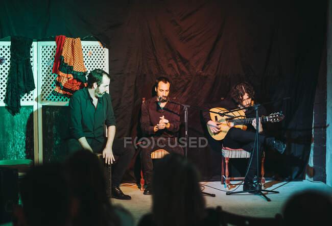 Groupe de musiciens hispaniques masculins en tenue noire assis sur des chaises en bois tout en jouant de la guitare acoustique et en chantant le chant flamenco dans le microphone sur la scène du théâtre en public — Photo de stock